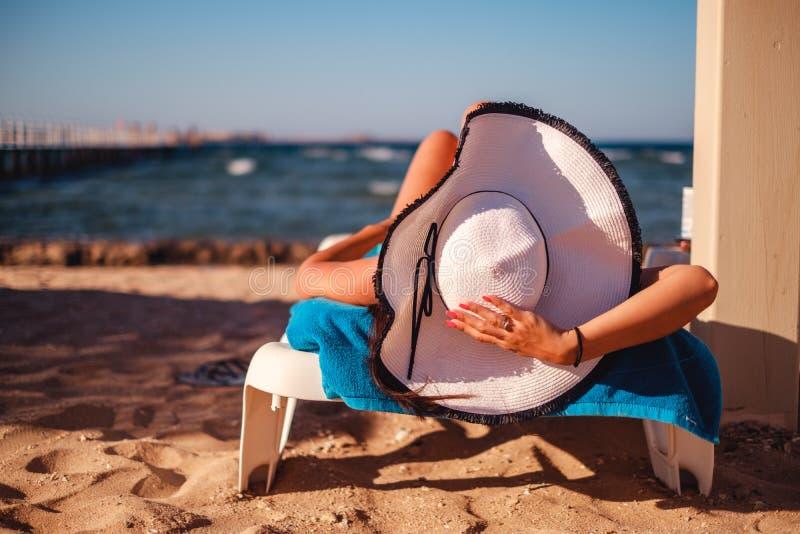 Hållande hatt för flicka, medan ligga på stranden royaltyfria foton