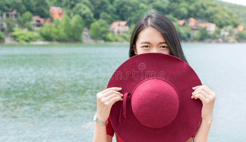 Hållande hatt för kvinna som framme står av en sjö royaltyfria foton