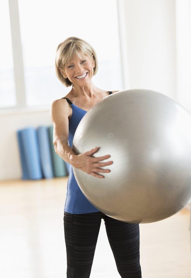 Hållande hemmastadd konditionboll för lycklig mogen kvinna arkivfoton