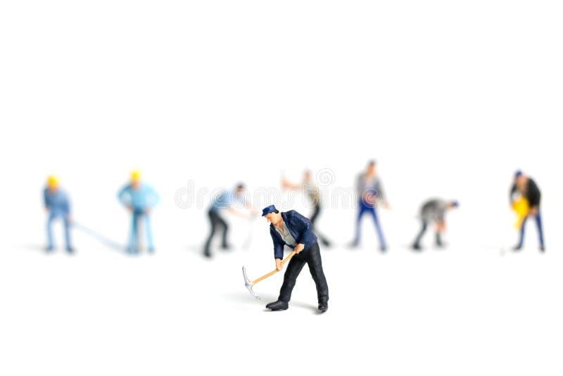 Hållande hjälpmedel för miniatyrfolkarbetare på vit bakgrund royaltyfri bild