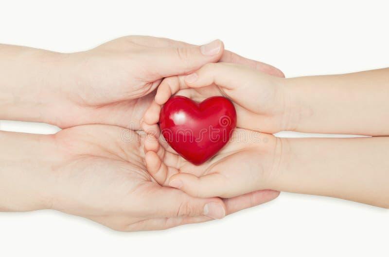 Hållande hjärta för förälder och för barn i hand arkivbild