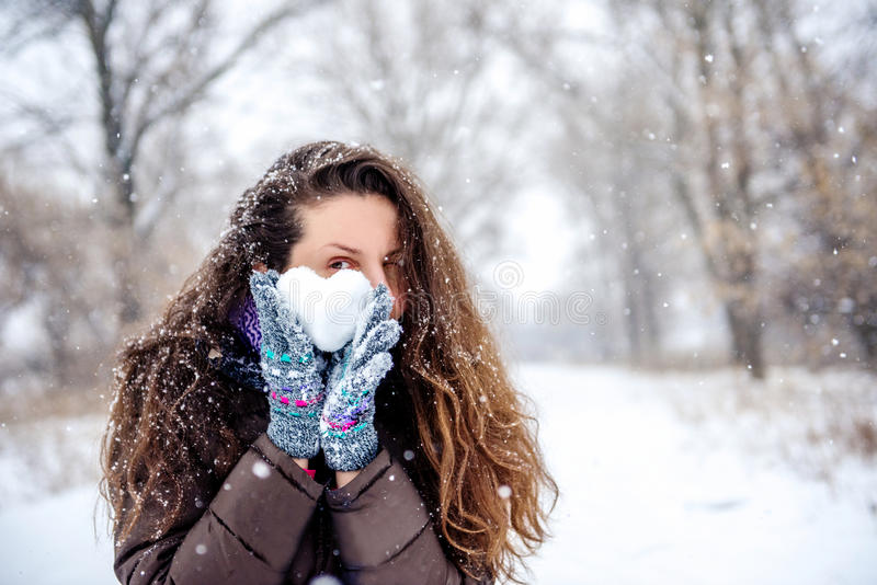 Hållande hjärta för kvinna som göras av snö royaltyfria foton