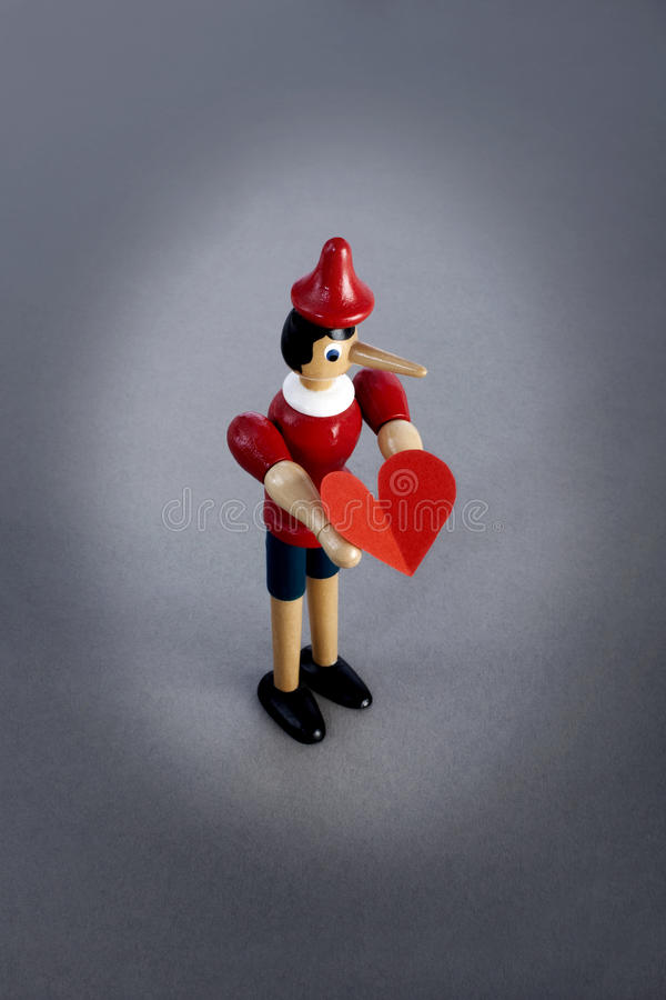 Hållande hjärta för Pinocchio lögnare arkivfoton