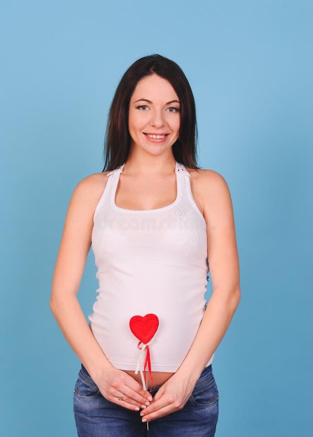 Hållande hjärta för Pregnnat kvinna på blått royaltyfri bild