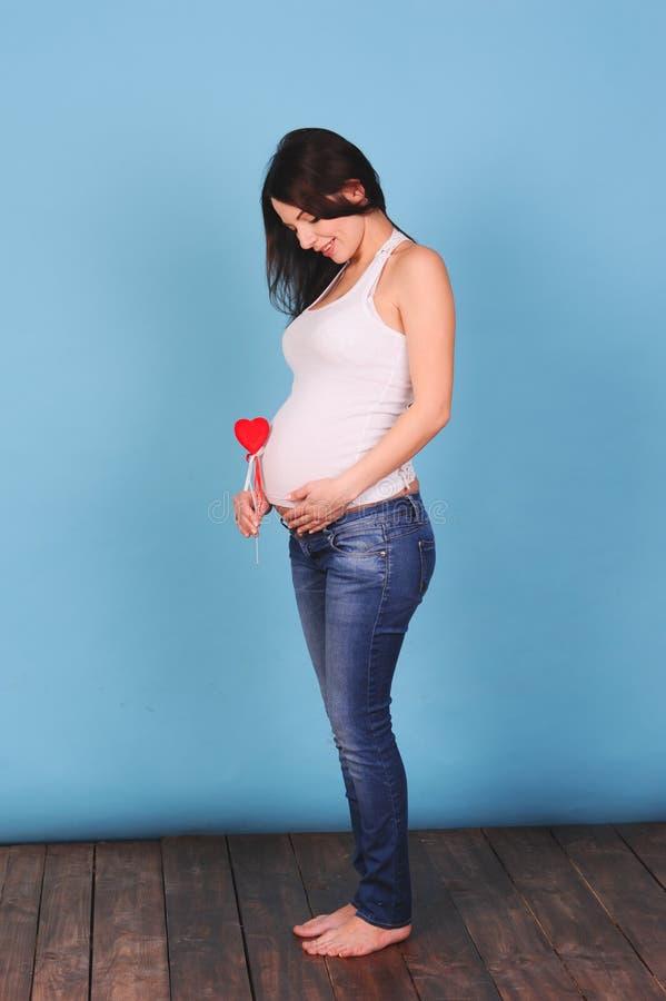 Hållande hjärta för Pregnnat kvinna på blått arkivfoto