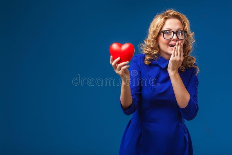 Hållande hjärtaform för rolig kvinna royaltyfri fotografi