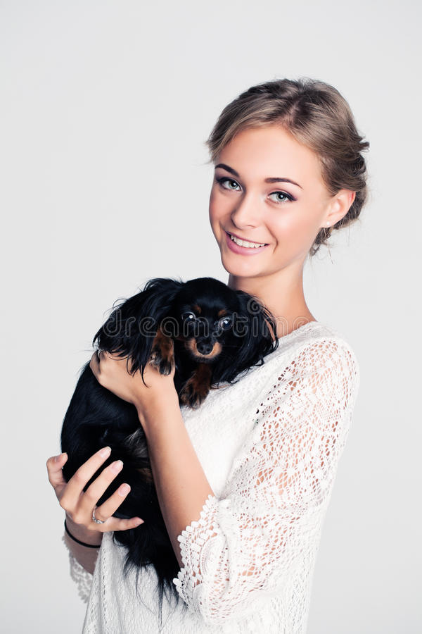 Hållande hund för modekvinna royaltyfria foton