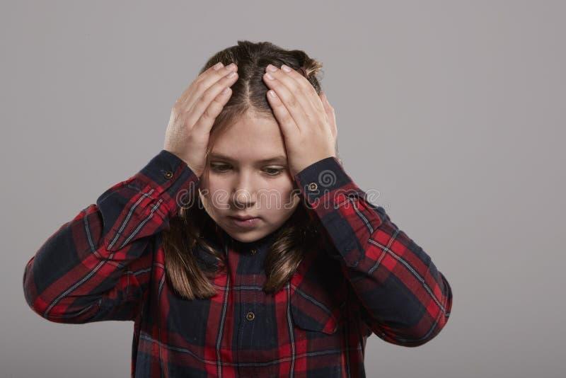 Hållande huvud för årig flicka tio i förvirring, midja upp royaltyfri bild