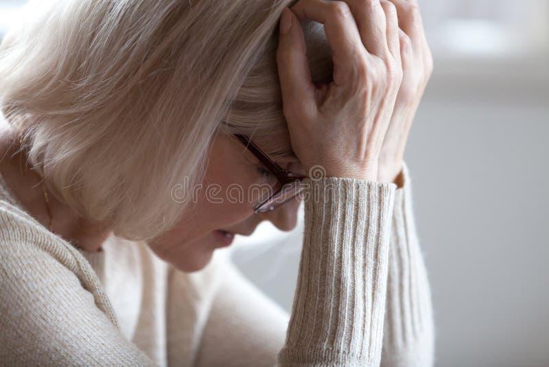 Hållande huvud för ledsen trött hög kvinna i händer som känner huvudvärk arkivbilder