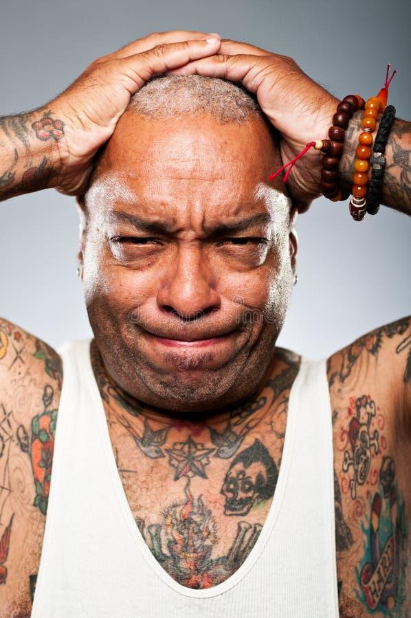 Hållande huvud för stilfull afrikansk amerikanman i frustration royaltyfria foton