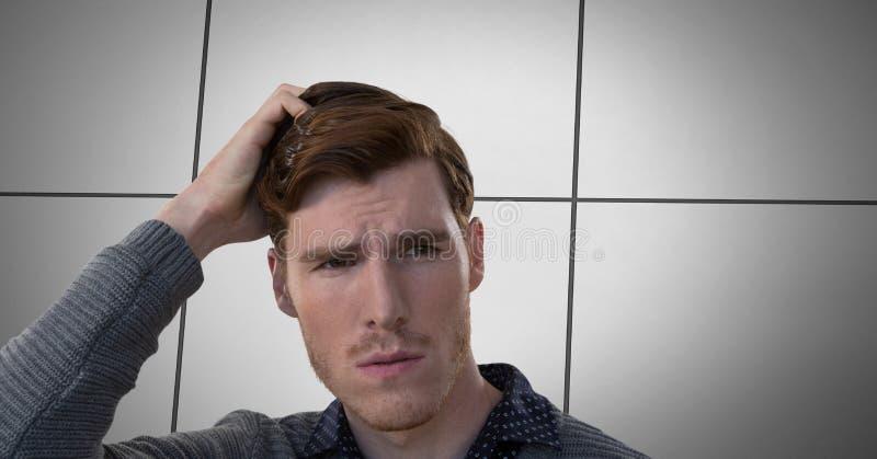 Hållande huvud för stilig affärsman som ser in i avstånd med den fodrade väggen royaltyfri bild