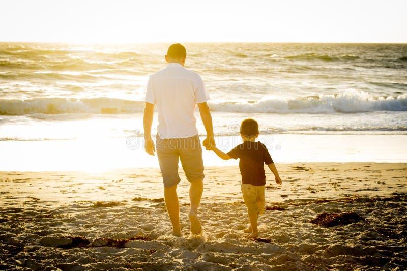 Hållande innehavhand för lycklig fader av den lilla sonen som tillsammans går på stranden med barfota arkivbilder