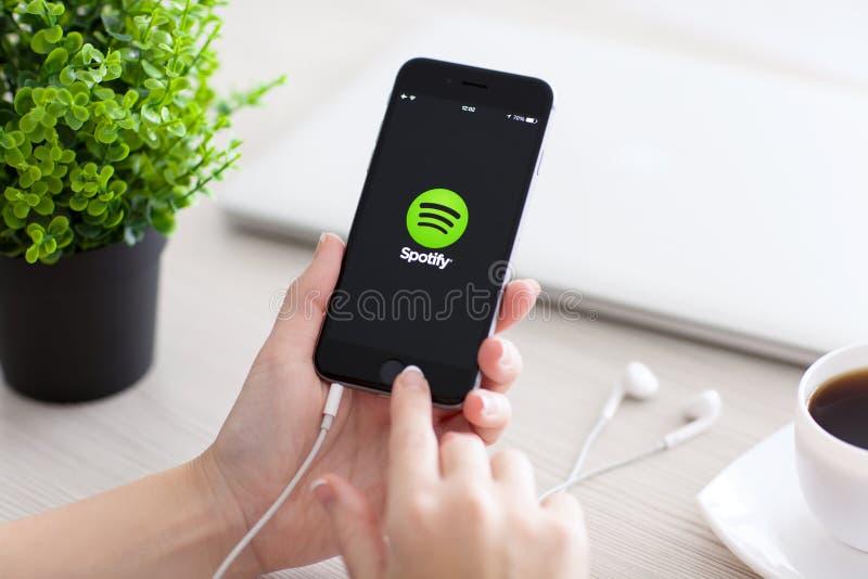 Hållande iPhone för flicka 6 utrymmegrå färger med tjänste- Spotify arkivfoton
