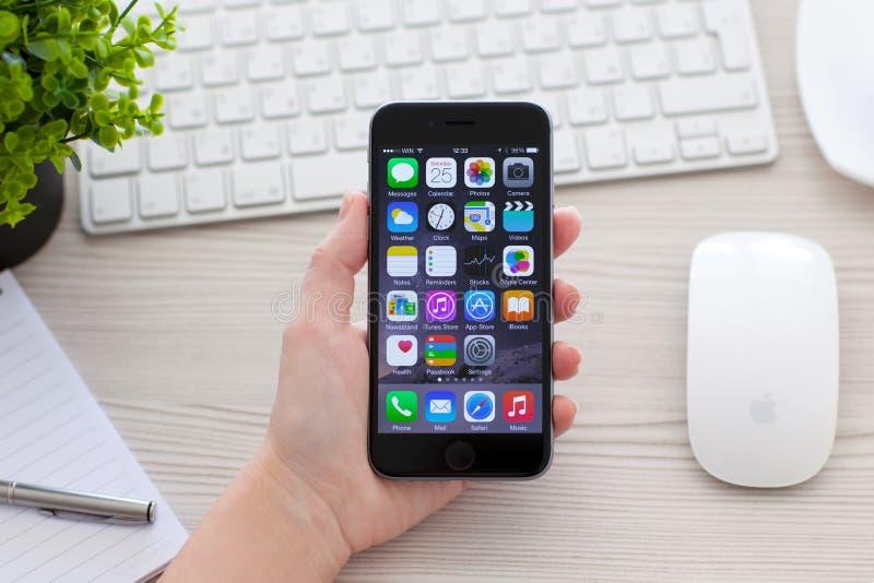 Hållande iPhone för kvinna 6 utrymmegrå färger över tabellen arkivbild