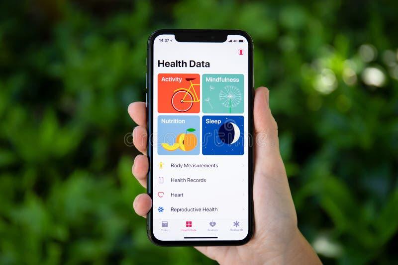 Hållande iPhone X för kvinnahand med app-hälsodata royaltyfria bilder