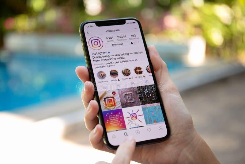 Hållande iPhone X för kvinnahand med social nätverkandeservice Insta arkivbilder