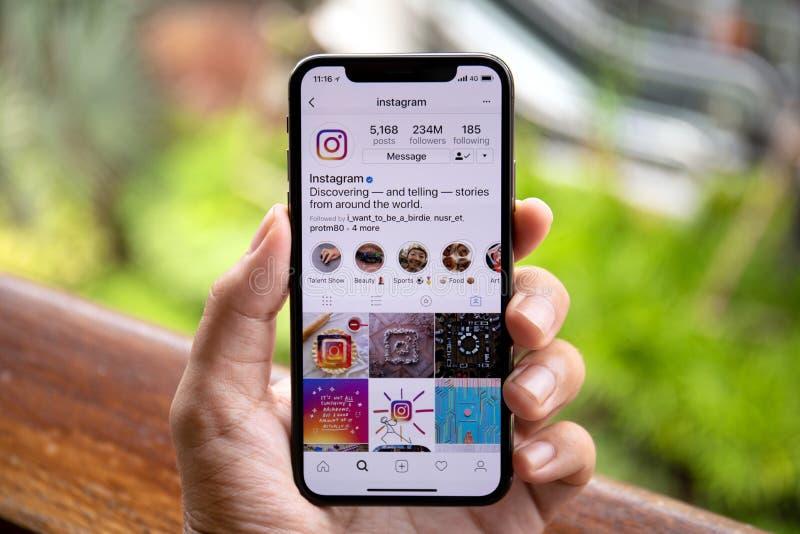 Hållande iPhone X för manhand med social nätverkandeservice Instagr royaltyfria foton
