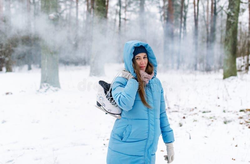 Hållande isskridskor för kvinna utomhus i snö royaltyfria foton