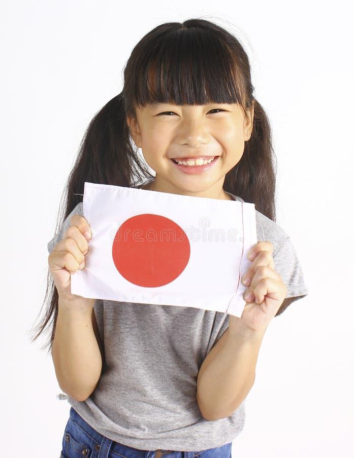 Hållande japansk flagga för gullig flicka royaltyfria foton