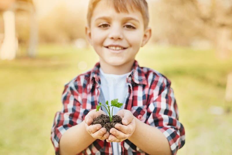 Hållande jord för positiv pys i händer royaltyfri foto
