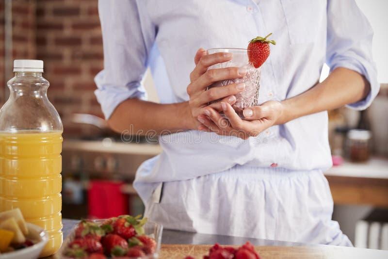 Hållande jordgubbesmoothie för kvinna, mitt- avsnitt royaltyfri bild
