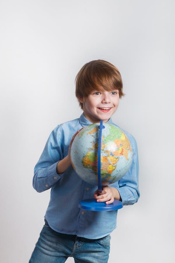Hållande jordklot för lycklig pys Dra tillbaka till skolan och lycklig tid royaltyfri fotografi