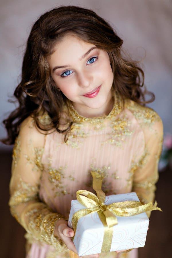 Hållande jul gåva, slut för härlig lockig ung flicka upp royaltyfria foton
