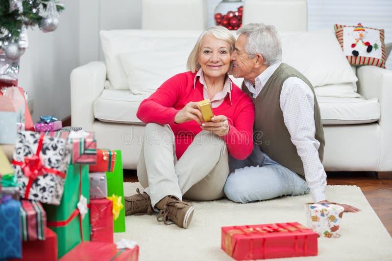 Hållande julklapp för kvinna medan man omkring till arkivbilder