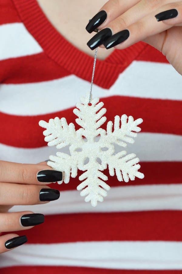 Hållande julsnöflinga för flicka royaltyfri foto