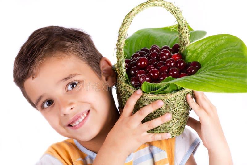 Hållande körsbärsröd korg för ung lycklig pojke royaltyfri bild