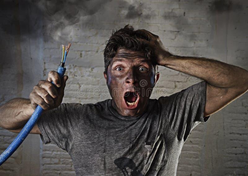 Hållande kabel för ung man som röker efter elektrisk olycka med den smutsiga brända framsidan i roligt ledset uttryck royaltyfri fotografi