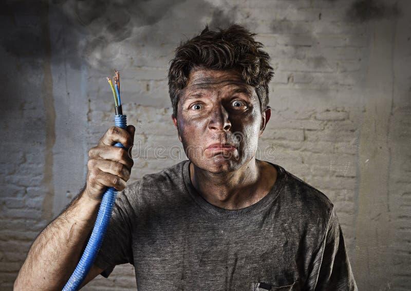 Hållande kabel för ung man som röker efter elektrisk olycka med den smutsiga brända framsidan i roligt ledset uttryck royaltyfria foton