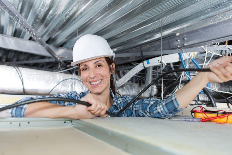 Hållande kablar för kvinna som är över huvudet i roofspace royaltyfri foto