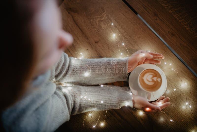 Hållande kaffe för flicka i händer över ljus bokehbakgrund Trevligt vinterfoto av händer med kaffekoppen med magiskt ljus royaltyfria bilder