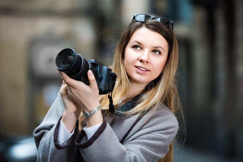 Hållande kamera för flicka i händer och fotografera i staden royaltyfri foto