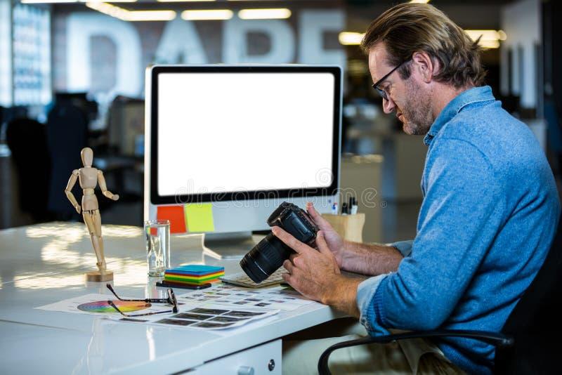 Hållande kamera för idérik affärsman på datorskrivbordet arkivbild
