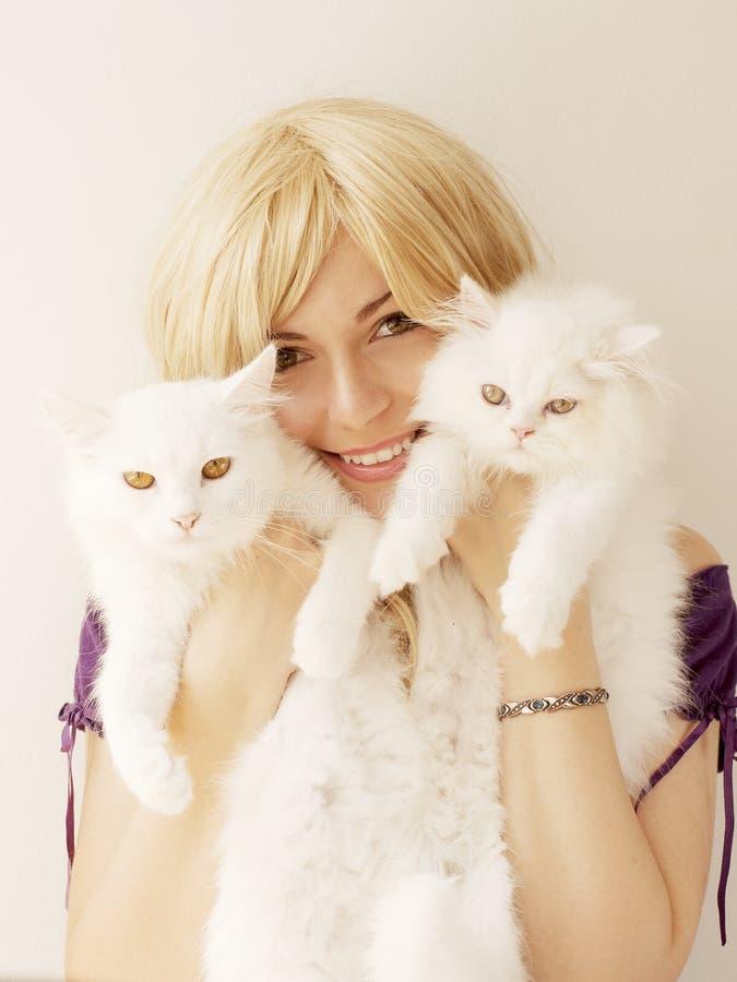 Hållande katter för flicka arkivfoto