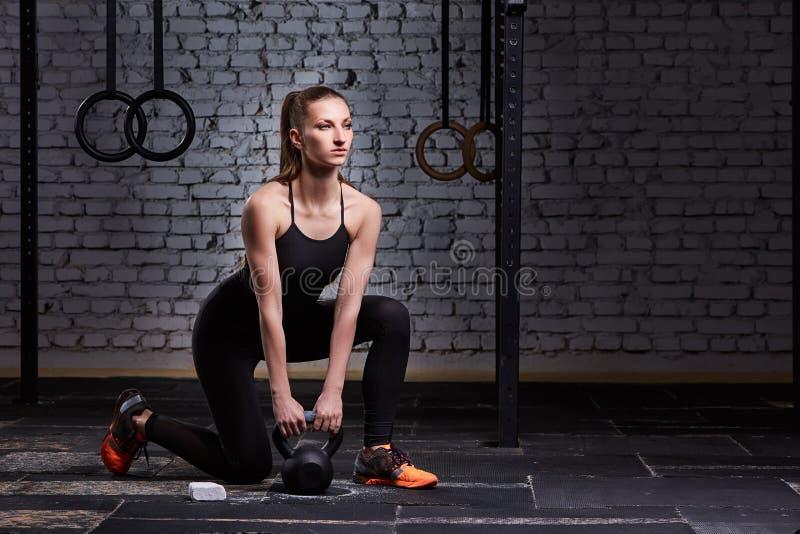 Hållande kettlebell för ung härlig sportig kvinna på idrottshallgolvet mot tegelstenväggen royaltyfria foton