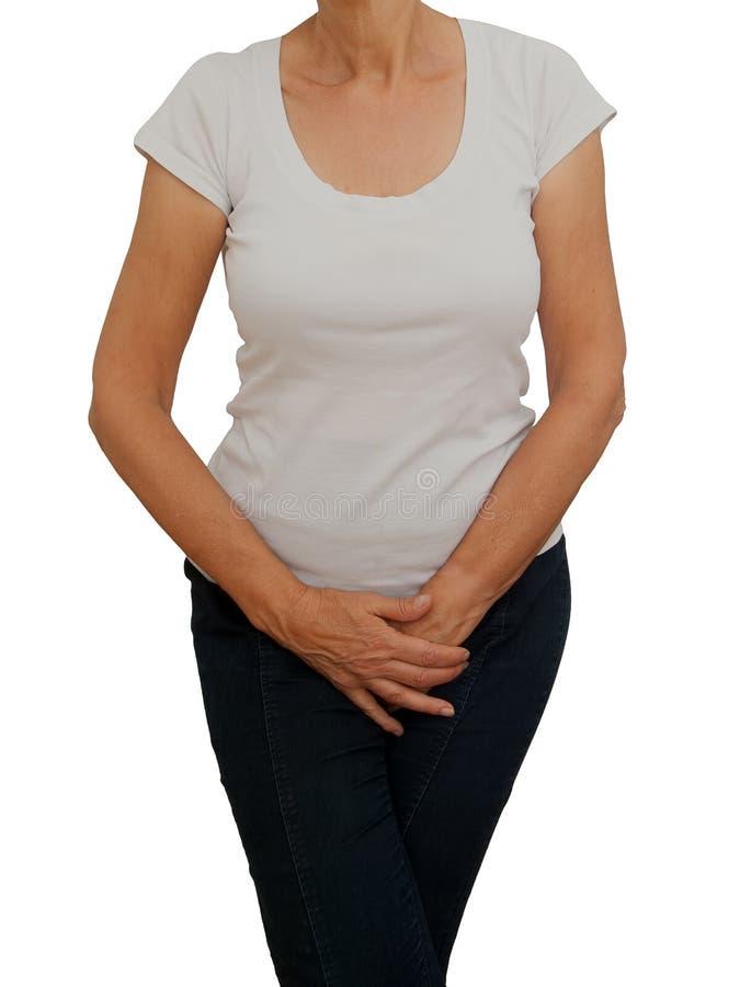 Hållande klyka för mogen äldre kvinna Förorsaka obehag från inkontinens, klimakterium eller liknande personligt problem Vit bakgr royaltyfria foton