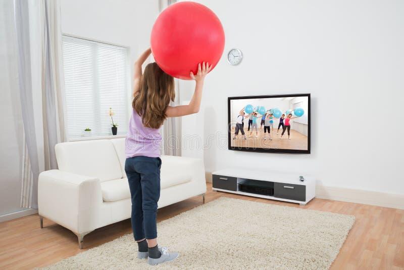 Hållande konditionboll för flicka i Front Of Television arkivbilder