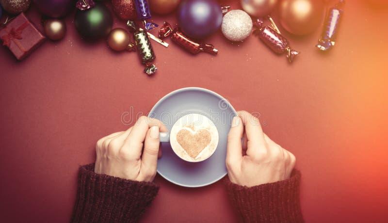 Hållande kopp kaffe för flicka nära julleksaker arkivfoton