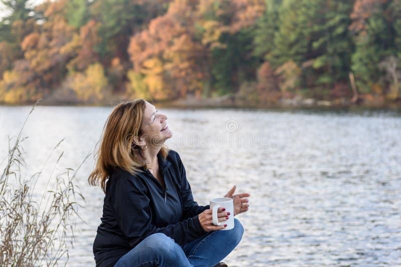 Hållande kopp kaffe för kvinna som skrattar längs lakefront med colorf royaltyfria foton