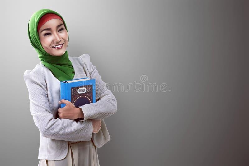 Hållande Koranen för nätt asiatisk muslimkvinna royaltyfri foto