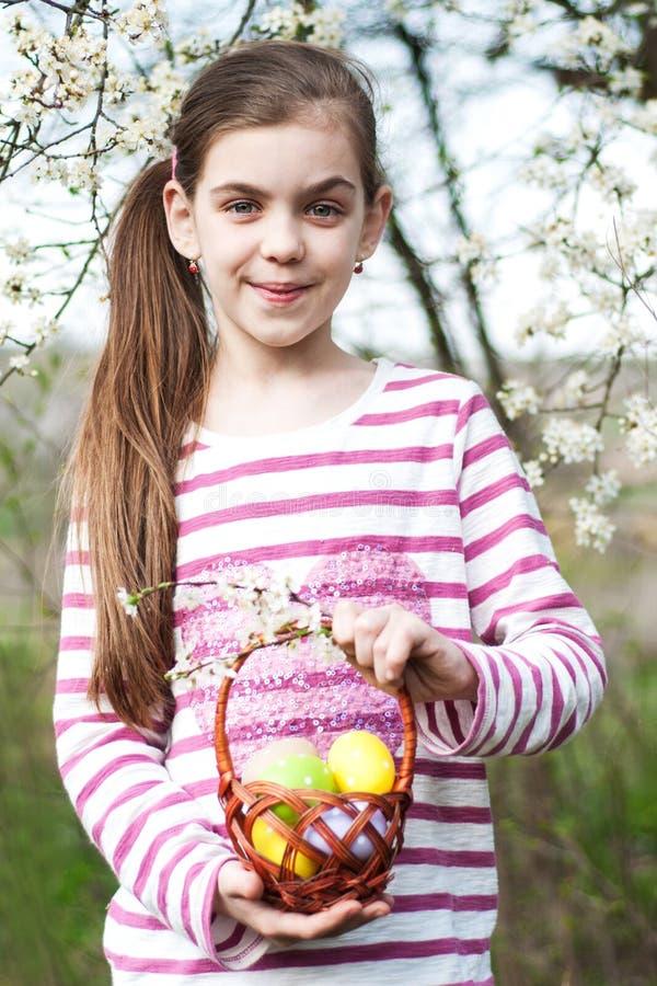 Hållande korg för flicka med easter ägg arkivfoto
