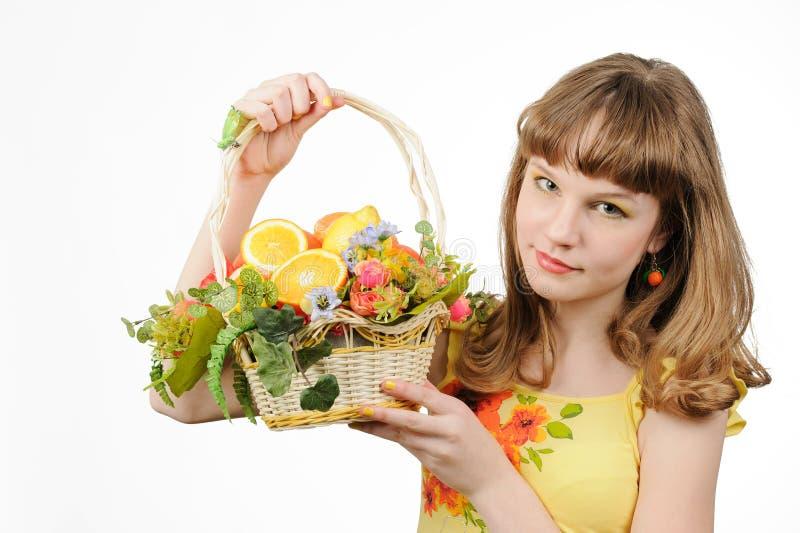 Hållande korg för flicka med frukter och blommor arkivbilder