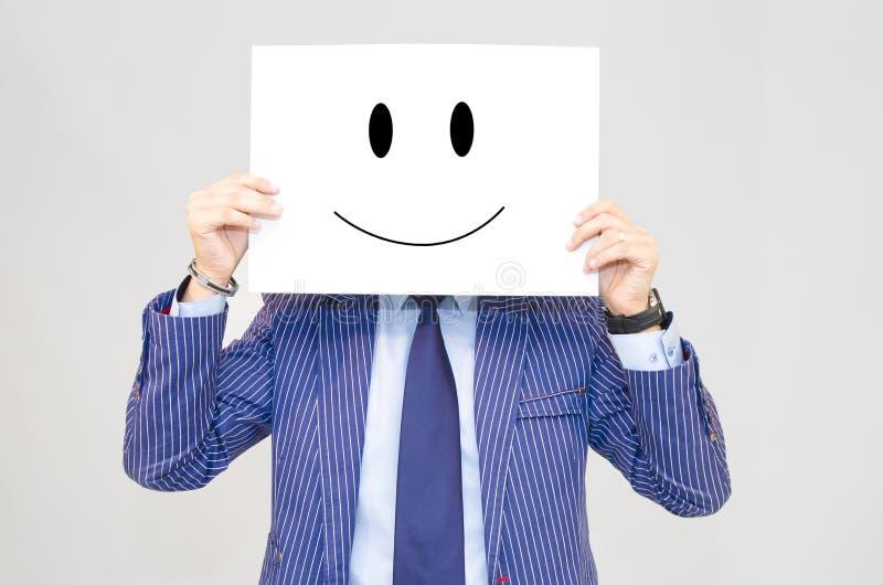 Hållande kort för affärsman med den lyckliga framsidan på grå bakgrund arkivfoto