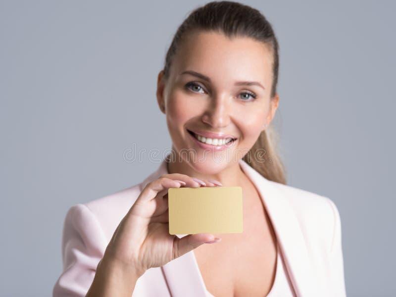 Hållande kreditkort för affärskvinna mot hennes isolerade framsida royaltyfri bild