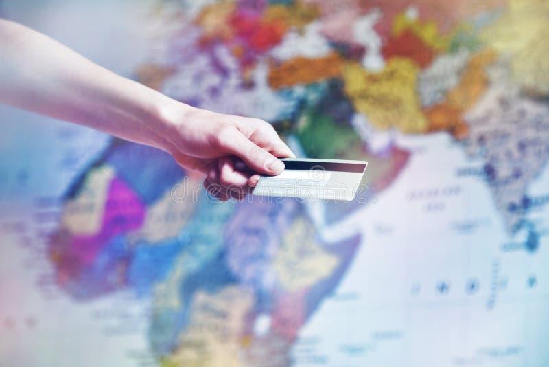 Hållande kreditkort för hand nära världskarta royaltyfri fotografi