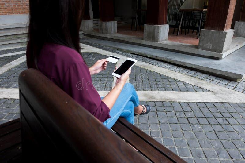 Hållande kreditkort för kvinna och användasmartphone för att shoppa onli arkivbild