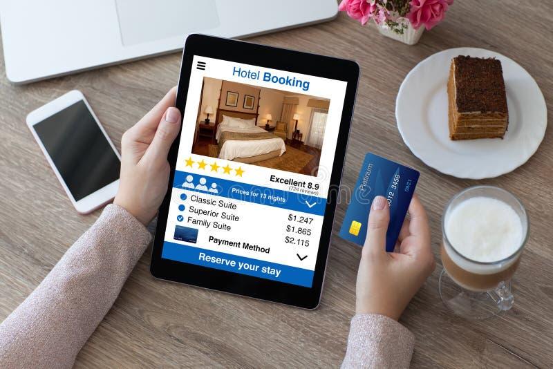 Hållande kreditkort för kvinna och bokning för hotell för datorminnestavlaapp royaltyfria foton